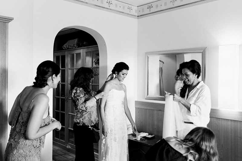 bride getting dressed with mother of the bride