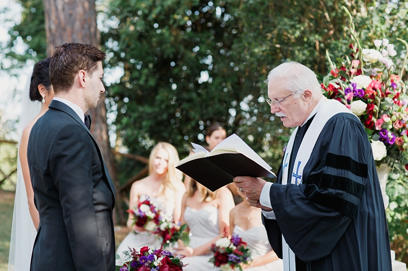 priest reading to bride and groom at destination wedding in tuscany